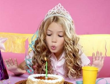 Девочка задувает свечу на розовом фоне