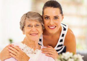 Молодая женщина обнимает пожилую
