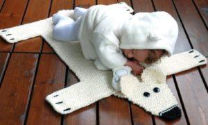 Малыш спит на вязанном медведе