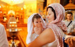 Крестная с девочкой в крыжме на руках
