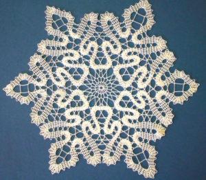 Связанная салфетка в виде снежинки