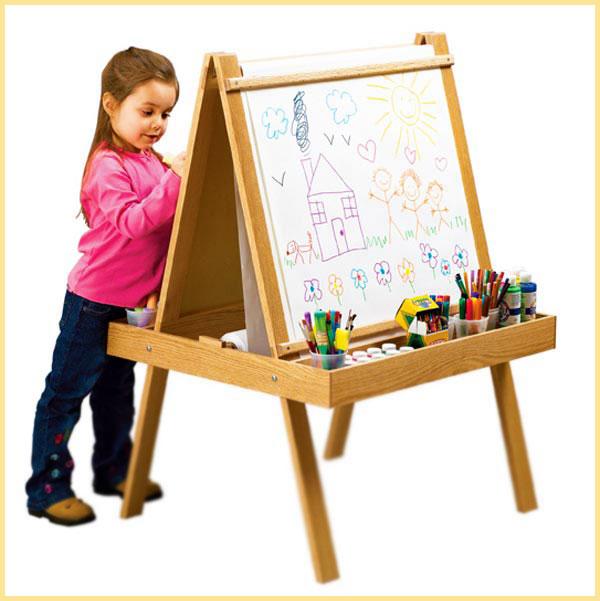 Девочка рисуте на мольберте